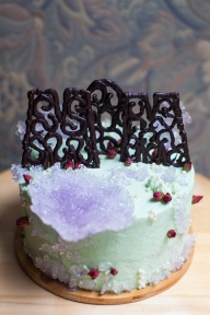 Sweet-smelling orange blossom & earl grey cake, with rosewater buttercream, deep pink rosebuds, lilac crystals & '♍️💟♏️' written in chocolate lace